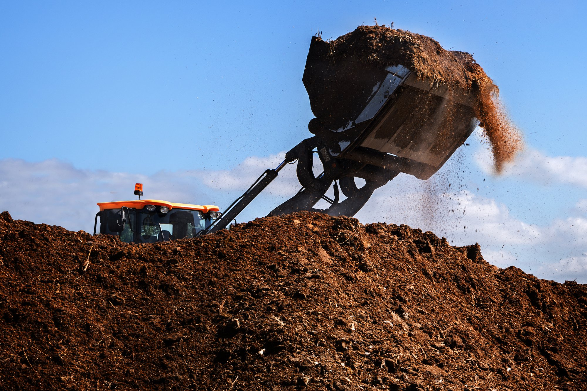 a tractor piling some compost